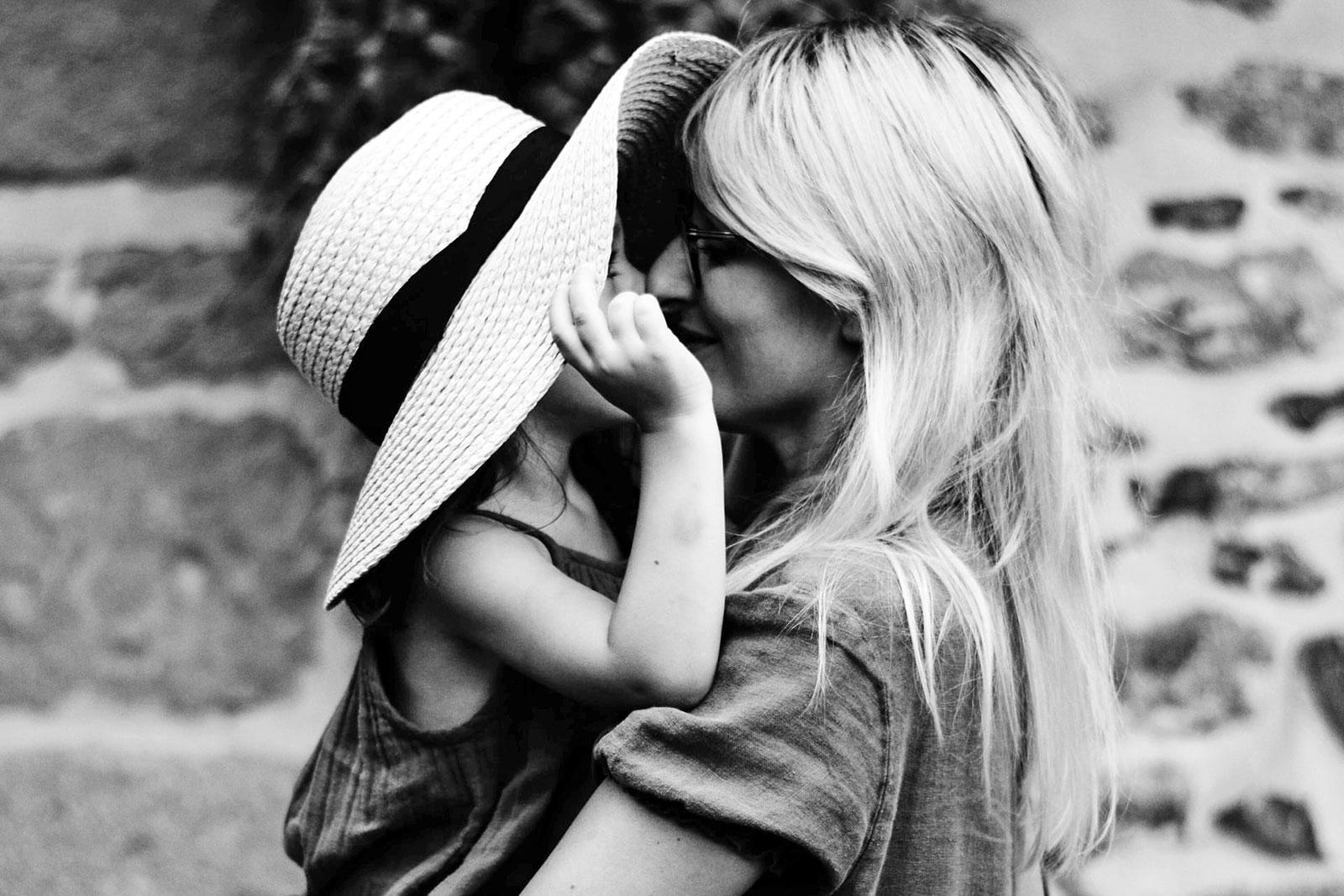Criança com chapéu de palha ao colo da mãe