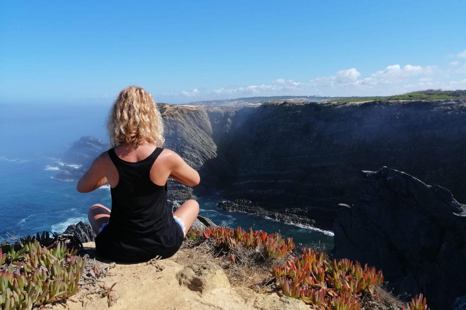 Mulher a fazer yoga sentada numa arriba junto ao mar