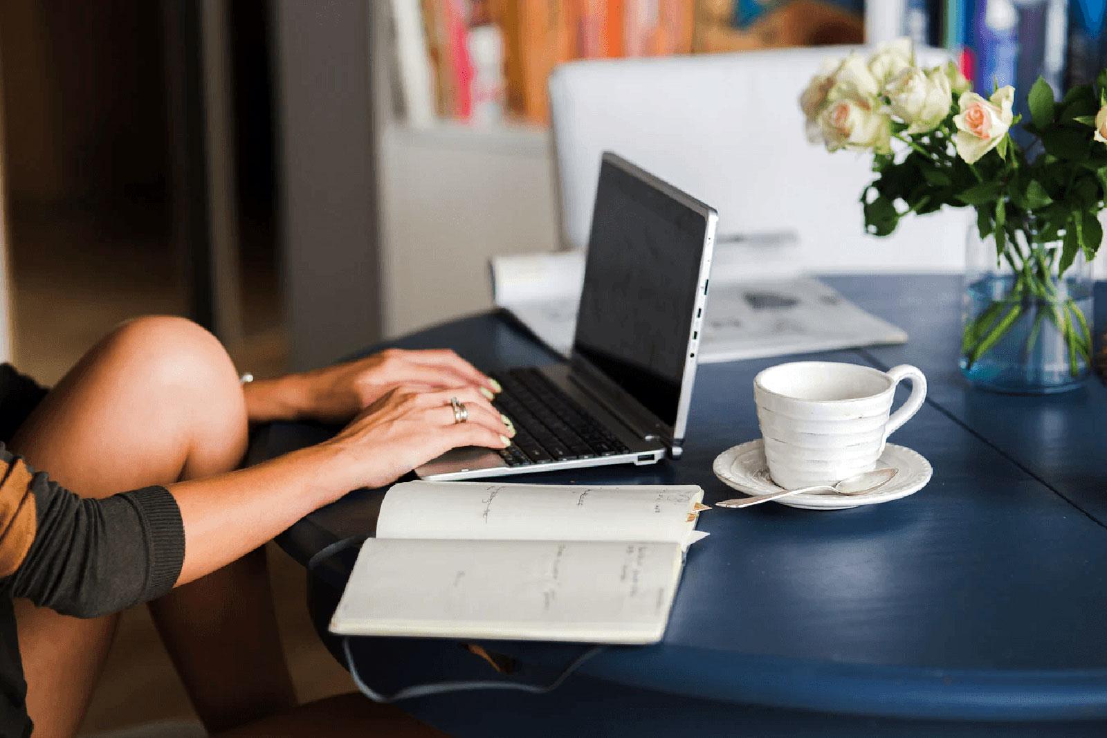 Mulher a trabalhar com laptop, sobre mesa com caderno e chávena