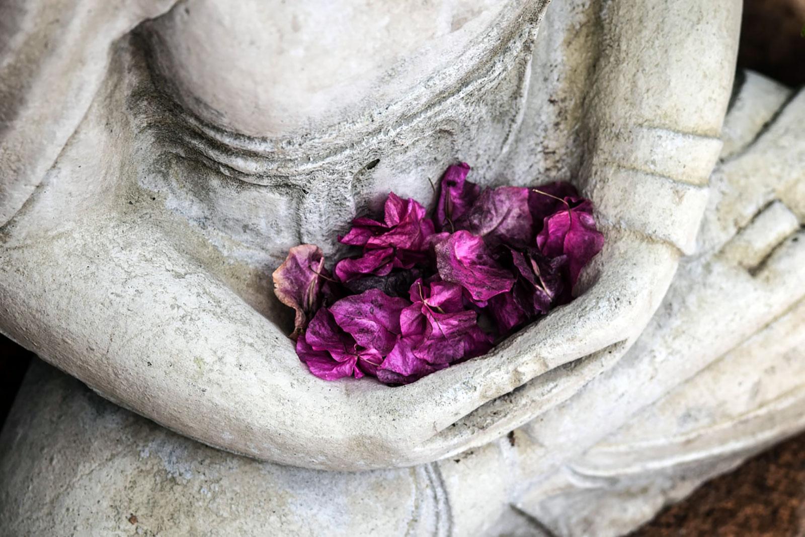 Estátua em pedra com figura a abraçar pétalas de flores.