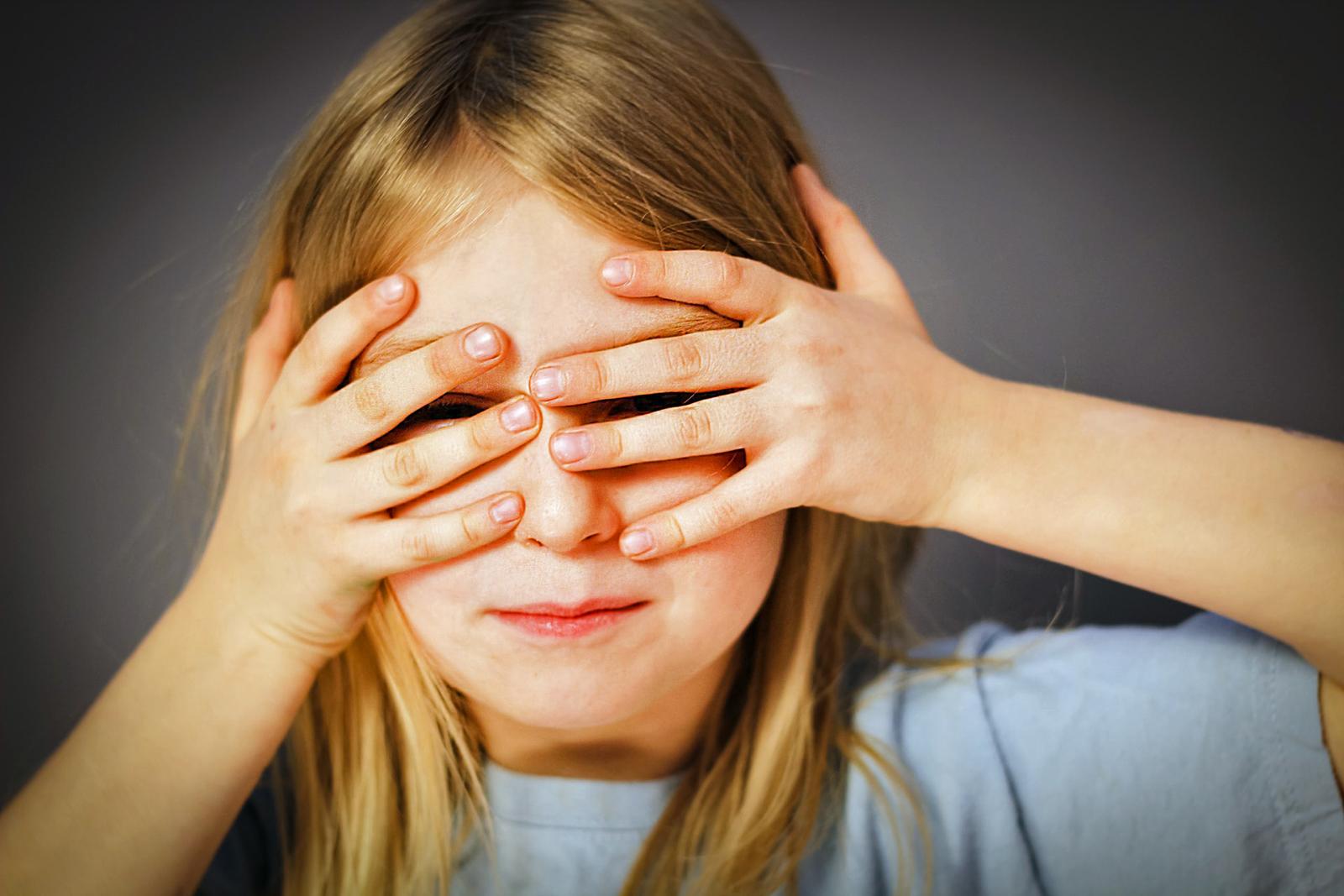 Criança a ver através dos dedos das mãos.