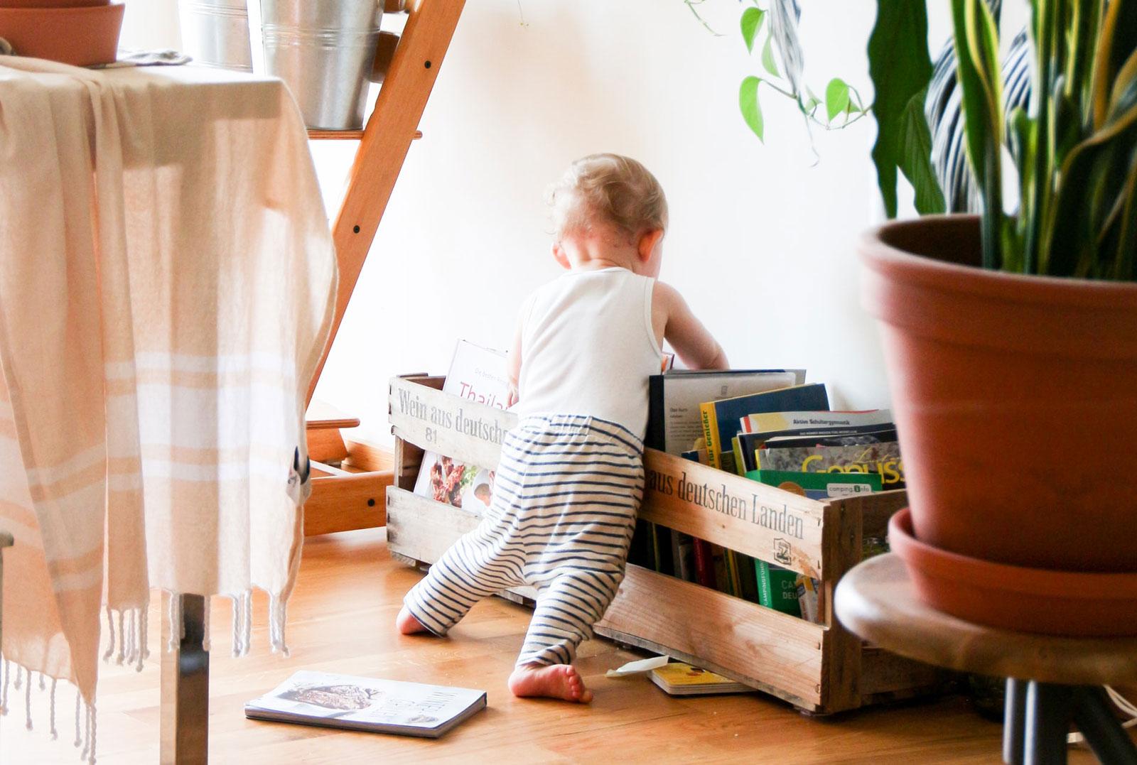 Criança junto a grande caixa de madeira cheia de livros